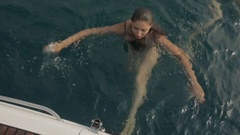 Sexy wet brunette swims up to the boat and climbs to its board Stock Footage