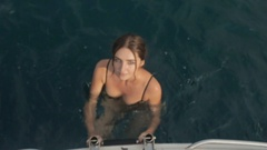 Attractive young wet woman in bikini climbs on a boat out of the sea Stock Footage