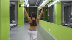 Young fitness woman doing lunge with barbell and flexing muscles in gym Stock Footage