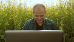 Young man in glasses sitting on the grass and typing on the laptop Stock Footage