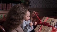 Young mother with her child at home warping gifts Stock Footage