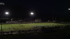 Aerial pan of high school football game at night Stock Footage