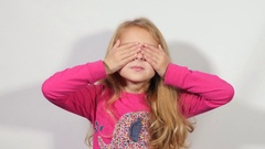 Girl blonde closes eyes with hands. A girl looks through fingers. Stock Footage