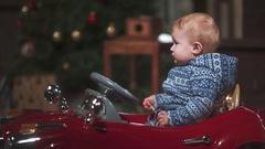 Boy riding a tiny toy car at xmas Stock Footage