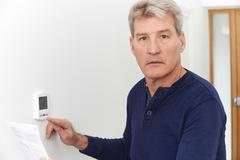 Worried Mature Man With Bill Turning Down Central Heating Thermostat Kuvituskuvat