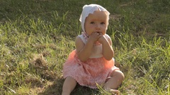 A baby girl fiddling with her dirty fingers in the mouth using both hands Stock Footage