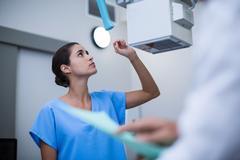 Nurse adjusting x-ray machine Stock Photos