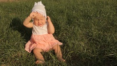 A baby girl rubbing her eyes with hands, the bright setting sun shining right Stock Footage