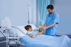 Male nurse giving teddy bear to patient during visit in ward Stock Photos
