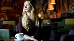 Worried girl sitting in the murky restaurant and looking around Stock Footage