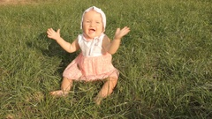 A baby girl trying to pull her bonnet off her head, waving hands and crawling Stock Footage