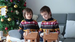 Adorable preschool children, boy brothers, decorating gingerbread houses for Chr Stock Footage