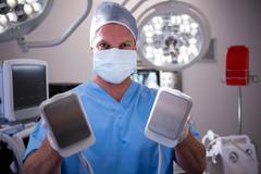 Portrait of male surgeon holding defibrillator Kuvituskuvat