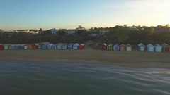 Flying low above water parallel to Brighton Beach bathing huts facing sun Stock Footage