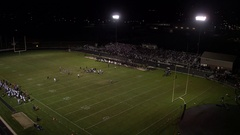 Aerial pan of high school football game at night Arkistovideo