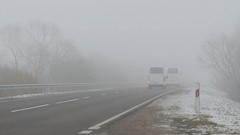 Cars ride on the road and shining lights in the fog Stock Footage