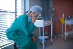 Tensed female surgeon sitting in ward Stock Photos
