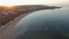 Slow descend over water facing the sunrise, Brighton Beach bathing huts Stock Footage