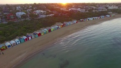 Fly rising high up and away from Brighton Beach bathing huts facing sunrise Stock Footage