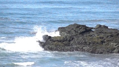 Slow motion wave hitting rocks with tall splash Stock Footage