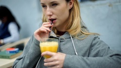 Happy girl sitting outdoors at cold day and drinking orange juice, steadycam sho Stock Footage