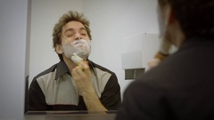 A close up montage of a young man shaving, washing his face, fixing his hair, Stock Footage