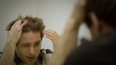 A frustrated man tries to fix his messy hair in the mirror. Stock Footage