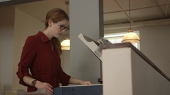 A medium shot of a woman using a photocopier in a modern office. Stock Footage