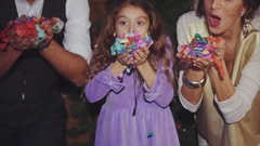 Happy family celebrating Christmas and New Year by blowing colorful confetti Stock Footage