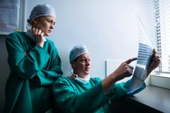 Surgeons sitting at window and checking x-ray Stock Photos