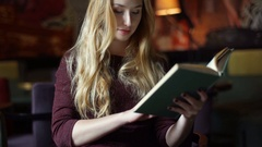 Absorbed girl sitting inside gloomy cafe and reading book, steadycam shot Stock Footage