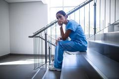 Upset female surgeon sitting on staircase Stock Photos