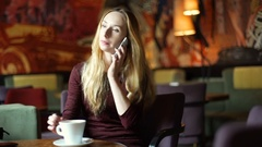 Happy girl sitting in the dark, cafe's interior and talking on cellphone Stock Footage