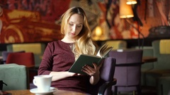 Girl receives message while reading book in the gloomy, dark restaurant Stock Footage