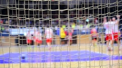 Handball match scene with goalpost net and players in the background Stock Footage