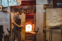 Glassblower heating a glass in glassblowers oven Stock Photos