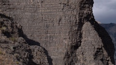Aerial panning view of rocky cliff face revealing Mountain Stock Footage