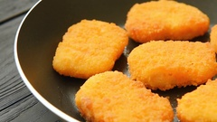 Cooked chicken nuggets in frying-pan Stock Footage