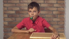 Child sitting at the desk holding flipchart with lettering happy birthday on the Stock Footage