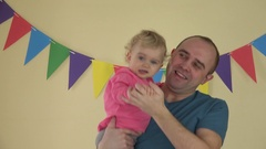 Family affairs - father with baby daughter in arms dancing at party Stock Footage