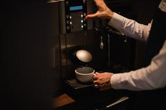 Waiter making cup of coffee from espresso machine Stock Photos