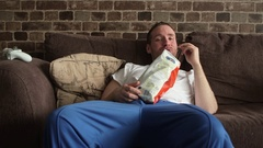 A lazy man sitting on his couch eating potato chips, watching TV and and Stock Footage