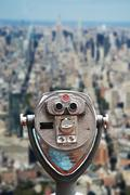 Coin operated binoculars on Top of the Rock, against Empire State Building Stock Photos