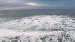 Flying backwards over ocean flowing over rocky shore Stock Footage