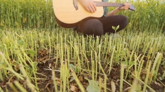 Young man playing a ukulele in a field sings energetically, in slow motion Stock Footage