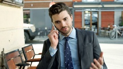 Businessman looking annoyed while talking on cellphone, steadycam shot Stock Footage
