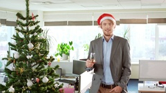 Handsome cheerful young blond businessman wearing christmas hat holding glass of Stock Footage