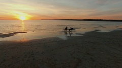 Aerial Shot of Two Girls Riding Horses on the Beach. Horses Walk on Water. Stock Footage