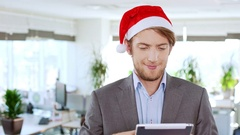 Handsome cheerful young businessman wearing christmas hat holding tablet showing Stock Footage