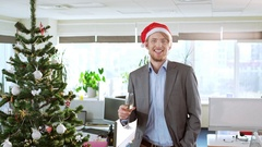Handsome young blond businessman wearing christmas hat holding glass of Stock Footage